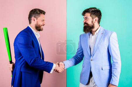 Photo for Business partners competitors office colleagues shaking hands. Tricky first impression. Do not trust him. Hidden danger. Businessman hides bat behind back while shaking hands. Hidden threat concept. - Royalty Free Image