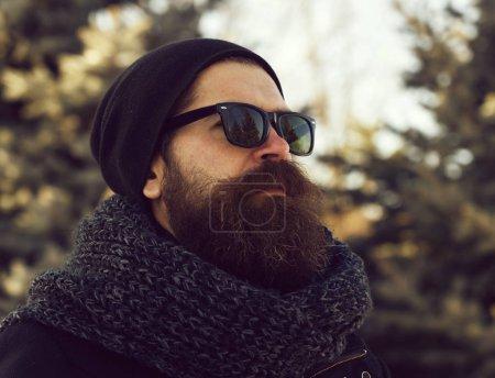 Photo pour Bel homme barbu, hipster, avec barbe et moustache en lunettes de soleil noires, chapeau et écharpe le jour d'hiver en plein air sur fond naturel flou - image libre de droit