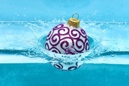 Photo for Christmas decoration or toy for Christmas tree swim in pool. Festive decoration for Christmas tree, silver ball dropped into water with splashes, blue background. Holidays and vacation concept. - Royalty Free Image