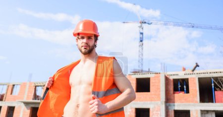 Photo for Guy protective helmet stand in front of building made out of red bricks. Builder orange vest helmet work construction site. Builder sexy muscular torso macho dream of every woman. Sexy macho foreman. - Royalty Free Image
