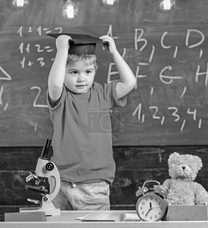 Photo for Kid boy in graduate cap ready to go to school, chalkboard on background. Child, pupil on smiling face near microscope. First former interested in studying, education. Kindergarten graduation concept. - Royalty Free Image