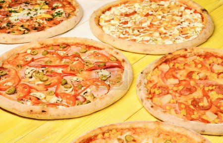 Photo pour Cercles de pizza avec viande, champignons, tomates et fromage sur fond de bois jaune. Concept de restauration rapide. Retirer la nourriture avec divers ingrédients et des bords croquants. Ensemble de pizza différent pour menu - image libre de droit