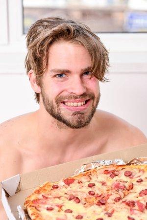 Photo pour Jeune homme au repos à la maison avec un nu et une pizza. Homme barbu beau bachelor manger fromage nourriture pour le petit déjeuner au lit. Concept de régime de pause. Partager repas - image libre de droit