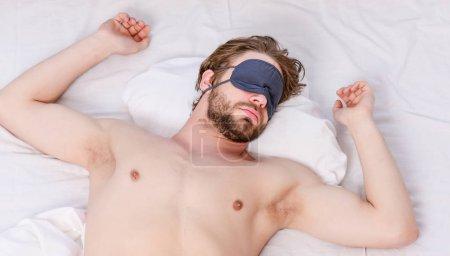 Photo pour Un bel homme bâillant et étirant les bras. Homme paresseux heureux de se réveiller dans le lit levant les mains le matin avec une sensation de fraîcheur détendue. Portrait de l'homme bâille et s'étire au lit - image libre de droit