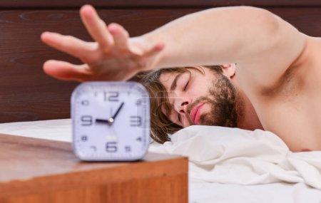 Photo pour Un jeune homme se réveiller dans son lit et en étirant ses bras. Homme qui s'étend dans son lit. Réveiller les hommes de matin - image libre de droit
