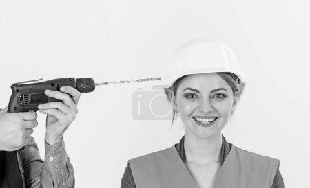 Photo pour Notion de contrainte de résistance. Femme heureuse et insouciante. Mains mâles avec perceuse tête de forets de femme, fond blanc. Femme au visage en casque, casque souriant. Perceuse fait un trou dans la tête féminine. - image libre de droit