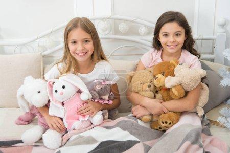 Photo pour Meilleur temps ensemble. Petits enfants s'amuser de Noël. Petites filles jouent avec des jouets. Enfants heureux dans son lit à l'arbre de Noël. Petits enfants profiter de Noël. Jeux de l'enfance sur Noël et nouvel an. - image libre de droit