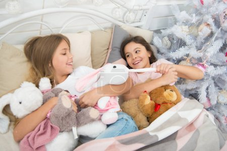 Photo pour Coquine et mignonne. Petites filles disputent des jouets. Actives petits enfants dans son lit à l'arbre de Noël. Petits enfants profiter de Noël. Petits enfants sont amuser de Noël. Jeux de l'enfance sur Noël et nouvel an. - image libre de droit