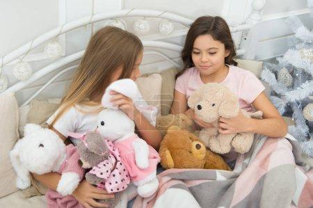 Photo pour Jeux de l'enfance sur Noël et nouvel an. Petits enfants profiter de Noël. Petits enfants sont amuser de Noël. Petites filles jouent avec des jouets. Enfants heureux dans son lit à l'arbre de Noël. Célèbrent Noël ensemble. - image libre de droit