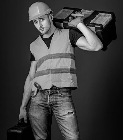 Photo for Man in helmet, hard hat holds toolbox and suitcase with tools, blue background. Worker, repairer, repairman, builder on calm face carries toolbox on shoulder, ready to work. Repair service concept. - Royalty Free Image