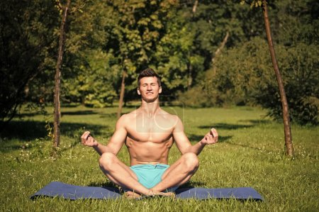 Photo for Man with healthy body meditate on yoga mat in summer park. Yoga, relax, zen, meditation, chakra, lotus, peace - Royalty Free Image