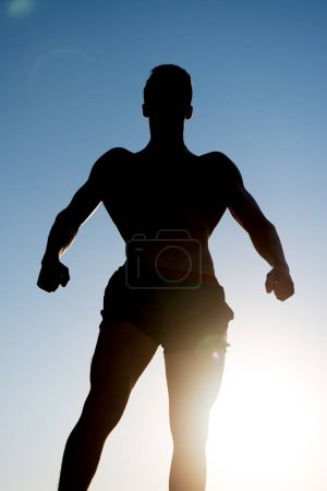 Photo for Bodybuilder posing on sky and sun light background. Athlete showing muscular body in dusk. Silhouette of strong man. Sportsman relaxing muscles, biceps, triceps outdoors. Fitness and sport concept. - Royalty Free Image