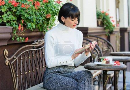 Photo pour Femme prendre un verre profiter d'une bonne terrasse café livre. Littérature pour femme. Une fille boit du café. Tasse de bon café et livre agréable meilleure combinaison pour un week-end parfait. Concept d'amélioration personnelle . - image libre de droit