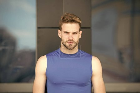 Photo for Man bristle serious face muscular shoulders, urban background, defocused. Metrosexual concept. Guy bearded and attractive cares about appearance. Man beard unshaven guy looks handsome and cool. - Royalty Free Image