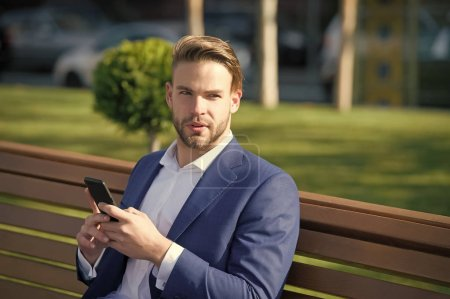 Photo for Message concept. Man types message mobile phone. Man in suit businessman takes advantages of modern mobile technologies. Businessman thoughtful face received important message, park background. - Royalty Free Image