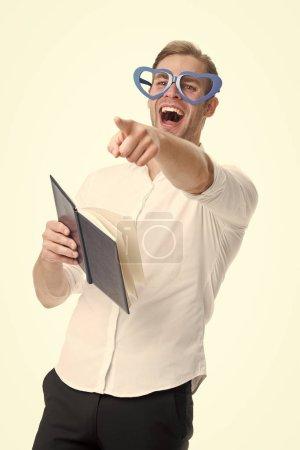 Photo pour Riez sincèrement. Homme beau jeune pointant vers l'avant et riant. Homme heureux souriant blond yeux bleus en forme de coeur lunettes avoir du plaisir. Guy avec livre riant isolé fond blanc . - image libre de droit