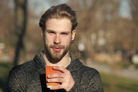 Photo pour Homme barbu avec une boisson à emporter sur l'air frais. Macho tenir la tasse à café jetable en parc ensoleillé. Ambiance de café ou de thé. Boisson et nourriture en plein air. Thé du matin pour le petit déjeuner. - image libre de droit
