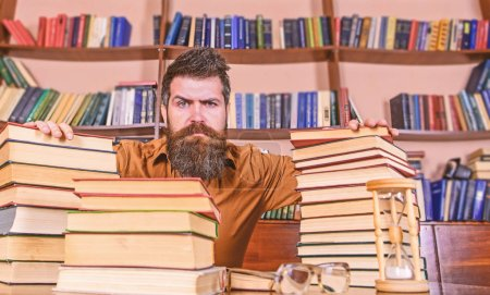 Photo for Teacher or student with beard sit at table with hourglass and glasses, defocused. Man on strict face sit between piles of books, while studying in library, bookshelves on background. Bookworm concept. - Royalty Free Image