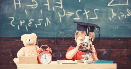 Photo for Kid boy in academic cap work with microscope in classroom, chalkboard on background. Child on busy face near microscope. Smart kid concept. First former interested in studying, learning, education. - Royalty Free Image
