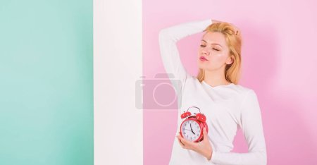 Photo for Lack of sleep bad for your health. Oversleeping side effects is too much sleep harmful. Girl drowsy face just woke up holds alarm clock pink background. Bad sleep habits and effects on your life. - Royalty Free Image