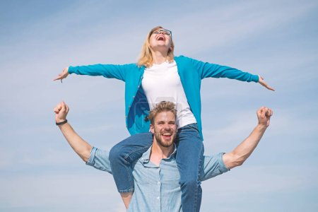 Photo for Couple in love enjoy feeling freedom outdoor sunny day. Couple happy date having fun together. Lovers enjoy date and feeling free. Freedom concept. Man carries girlfriend on shoulders, sky background. - Royalty Free Image