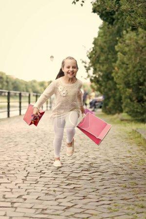 Photo pour Concept de shopping. Jolie petite fille courant dans la rue avec les sacs à provisions roses - image libre de droit