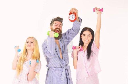 Bearded man holds alarm clock. Cheerful friends wi...