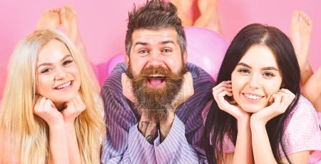 Photo for Cheerful morning concept. Man and women, friends on smiling faces lay, pink background. Lovers in love happy together. Bearded man and women in domestic clothes, pajamas. Threesome relaxing in morning - Royalty Free Image