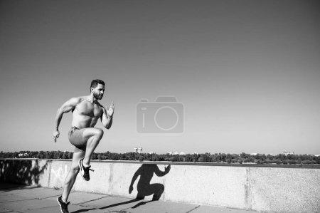 Photo pour Homme athlète musclé torse d'entraînement en plein air. La course du matin est pleine d'énergie. Matin d'entraînement des coureurs au lever du soleil. Motivation et réalisation. Habitudes matinales. Mouvement du coureur vers l'avant fond du ciel . - image libre de droit