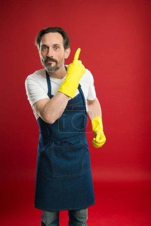 Sie sollten es sehen. Ältere Haushaltshilfen präsentieren etwas. Reifer Mann mit erhobenem Zeigefinger. Ein älterer Herr mit Latzschürze und gelben Gummihandschuhen. Erbringung von Haushaltsdienstleistungen