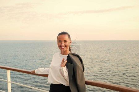 Photo pour Femme heureuse avec une veste d'affaires à bord du navire à Miami, Etats-Unis. Voyager pour affaires. Femme sensuelle sourire à bord du navire sur la mer bleue. Mode, beauté, regarde. Wanderlust, aventure, découverte, voyage . - image libre de droit