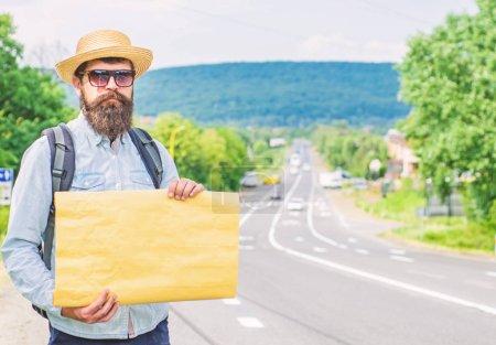 Photo pour Ramasse-moi. Homme barbu auto-stoppeur debout au bord de la route avec panneau en papier blanc, espace de copie. Avantages en utilisant signe avec la destination de nom. Panneau en carton avec indication où vous voulez aller . - image libre de droit