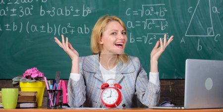 Photo for It is time. teacher with alarm clock at blackboard. Time. Back to school. Teachers day. Study and education. Modern school. Knowledge day. School. Home schooling. happy woman. woman in classroom. - Royalty Free Image