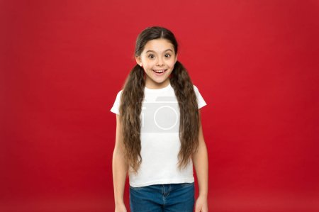 Photo for Happiness and joy. Positive emotions. Child care and upbringing. Kid smiling cute face live carefree happy life. Enjoy every moment. Young and free. Happy child girl with long hair on red background. - Royalty Free Image