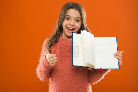 Photo for Starting to learn more. Girl hold book orange background. Child show open pages of book or notepad. Book store concept. Free books available to read. Childhood literature. Development and education. - Royalty Free Image