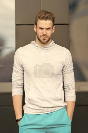 Photo for Sport fashion concept. Guy bearded and attractive cares about appearance. Man with bristle on serious face in sporty wear, urban background. Man with beard or unshaven guy in stylish sport clothes. - Royalty Free Image