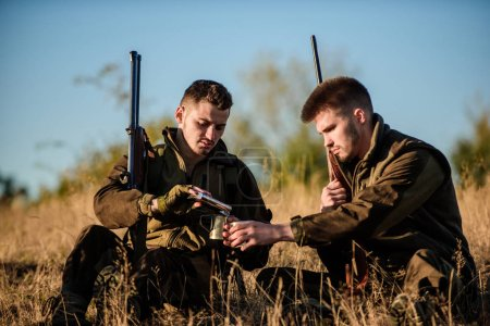 Photo for Hunting with friends hobby leisure. Hunters satisfied with catch drink warming beverage. Rest for real men concept. Hunters with rifles relaxing in nature environment. Hunters friends enjoy leisure. - Royalty Free Image