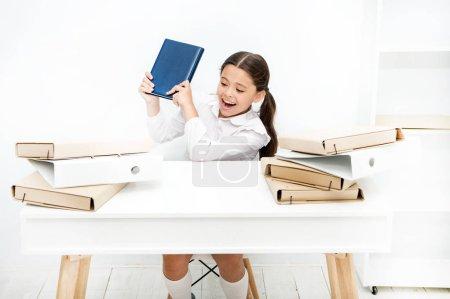 Photo pour Une fille capricieuse. Petite fille soulevant le livre dans les dossiers. Une fille en colère déteste lire un livre. Vilain enfant bruyant à l'école. Petit enfant refusant de lire l'alphabétisation. Écolière ayant une leçon de littérature . - image libre de droit