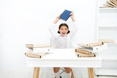 Photo pour D'humeur capricieuse. Vilain enfant bruyant à l'école. Petit enfant refusant d'apprendre l'alphabétisation. Petite fille soulevant livre au-dessus de la tête. Une fille en colère déteste lire un livre. Écolière ayant une leçon de littérature . - image libre de droit