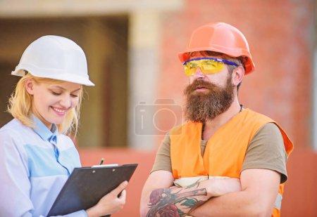 Photo pour Concept d'inspecteur de sécurité. Inspecteur de la femme et le Barbu constructeur brutale discutent des progrès de la construction. Inspection de projet de construction. Contrôle de sécurité de site de construction. Discuter des progrès projet. - image libre de droit