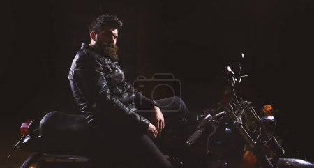 Photo for Man with beard, biker in leather jacket sitting on motor bike in darkness, black background. Macho, brutal biker in leather jacket riding motorcycle at night time, copy space. Night racer concept. - Royalty Free Image