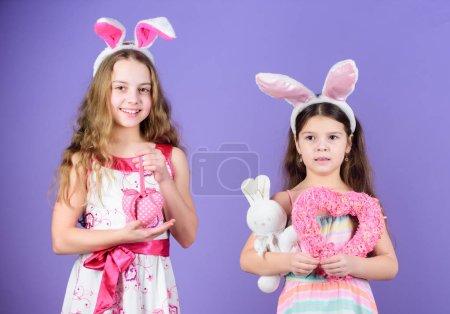 Photo pour Qui dit qu'il n'y a pas de lapin de Pâques. Petits enfants dans les bandeaux de lapin de Pâques. Enfants mignons dans le style lapin de Pâques tenant des cœurs. Des petits enfants portant des oreilles de lapin. Enfants célébrant Pâques . - image libre de droit