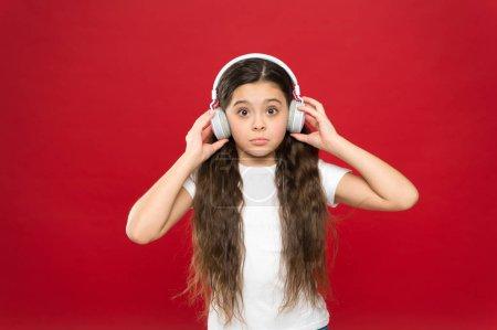 Photo pour Ce qui est toute cette histoire. Petite fille qui porte un casque stéréo. Fan de musique mignon avec casque sans fil. Petit enfant utilisant la technologie pour les loisirs et l'éducation. Petite fille, écouter de la musique. - image libre de droit