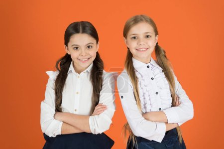 Photo for Keeping arms crossed. School children with a fashion forward look. Cute schoolgirls. Little girls wearing school uniform. Stylish girls in pigtails dressed for school. Back to school fashion style. - Royalty Free Image