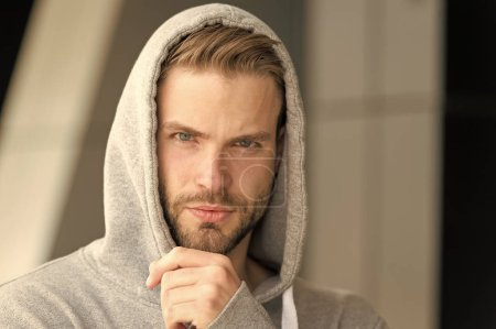 Photo for Let me think. Guy bearded thoughtful touches bristle on chin. Thoughtful mood concept. Man with beard or unshaven guy looks handsome hooded. Man with bristle serious face, urban background, defocused. - Royalty Free Image