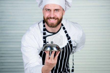 Photo pour Trucs de restaurant gai et poli. Maître cuisinier de servir des repas au restaurant. Chef cuisinier en uniforme debout avec plat délicieux. Bel homme en chapeau tablier et cuire. C'est un vrai maître cuisinier. - image libre de droit