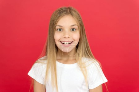 Photo for Brilliant smile concept. Girl cute smiling face over red background. Emotional kid happy smiling face. Sincere emotion. Cheerful adorable girl smiling. Positive and optimistic. Smiling beauty. - Royalty Free Image