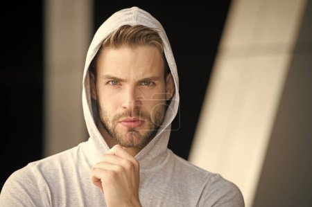 Photo for Focused future achievement. Guy bearded attractive casual clothes hooded. Man with bristle concentrated face urban background defocused. Man unshaven guy looks handsome hooded. Concentrated on goal. - Royalty Free Image
