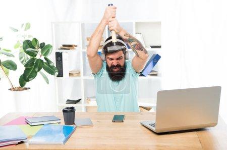 Photo pour Homme barbu guy casque bureau marteau smartphone. Communication gâtée. Échec des négociations mobiles. Plus ennuyeux sur le travail en centre d'appels. Appel entrant. Travail stressant au centre d'appel. - image libre de droit