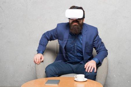 Photo pour Virtuel espace bureau et le travail. Homme d'affaires sit chaise usure hmd explorer la réalité virtuelle ou partenaire d'affaires ar. interagir en réalité virtuelle. Nouvelle opportunité. Entreprise mise en oeuvre de la technologie moderne. - image libre de droit